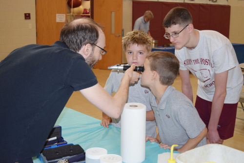 Pierre St-Laurent explaining the use of a refractometer to kids during STREAM Day (science outreach, May 2017)
